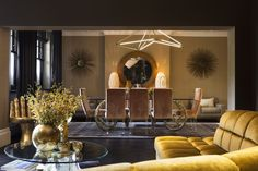 opulent and chic gold reception living and dining room with gold sofa and  contemporary chandelier Moody interior scene of chair  by Nathalie Priem interiors photographer