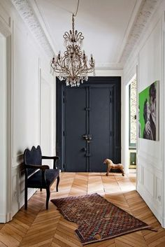 Chevron wood floors, black door, chandelier... everything but the crooked throw rug. What's up with that?