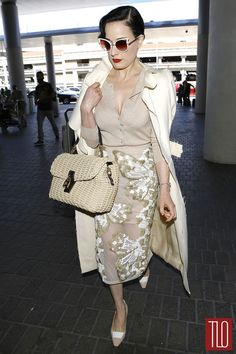 Dita Von Teese catches a flight out of LAX and arrives in Nice, France in a Blumarine skirt accessorized with a Dolce&Gabbana bag and Dita Von Teese eyewear.