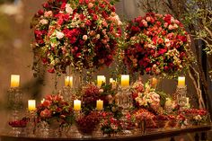 Beautiful candy table with elegant arrangements of red and pink flowers and candles