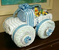 Monster Truck diaper cake baby shower 30 diapers each wheel, 30 for cab and engine, rolled blanket&bottles for lights, box for bed, wrap all in blanket supported by pc of cardboard, tac with tap & secure with ribbon.set body on axils(paper towel tubes). Bib for front&back windows. Bib for back mud flap(cant see in pic) to hid back axil. Cardboard cut circles with ribbon for hub caps