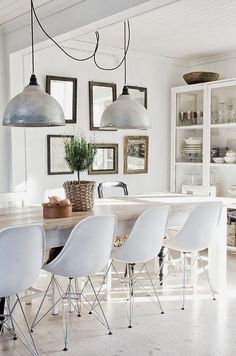 Tip on how to mix styles with confidence: keep it monochrome. The farmhouse table, mid-century seating and industrial pendants look perfect together, because they're all in the same white/silver range.