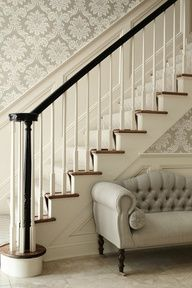 ML Interior Design: Elegant foyer with silver gray damask wallpaper paired with wainscoted staircase wall and glossy black staircase banister with white spindles. Gray tufted camelback French settee with matching bolster pillows and caster legs.