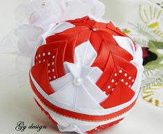 This quilted ornaments are made of white, red and dots satin ribbon placed on a…