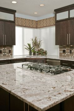 Sleek Contemporary Kitchen Design With Dark Solid Wood Cabinetry And White Springs Granite Countertop Glass Tile Backsplash. Corner window like ours