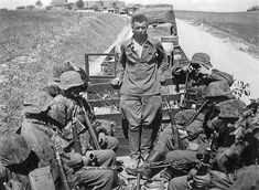 German truck column with SS soldiers. The person at the center is a Russian POW