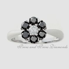 """Centre stone is a 0.14ct GH/VS – SI round brilliant cut diamond with 6 = 0.60ct round cut black diamonds in an 18k white gold """"flower"""" setting"""