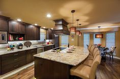 Imposing dark wood island and matching cabinetry stand out in this sand toned kitchen over natural hardwood flooring. Marble countertops and white brick backsplash add variety of texture.