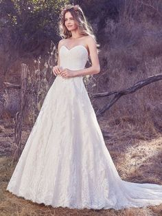 Maggie Sottero - OLEA, Cascades of breathtaking lace motifs elevate this timeless A-line wedding dress, featuring a subtle sweetheart neckline and a scalloped lace hem. Finished with covered buttons over zipper and inner corset closure.