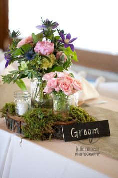 Rustic woodland centerpiece by Sachi Rose. Wood slices, moss and mason jars - perfect for a country wedding!