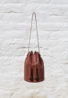 Bucket in Brick a classic bucket bag 32 × 21 cm, strap drop 33 cm $485.00   Smooth brick colored leather, Leather shoulder strap, Leather tassels, Leather lined base