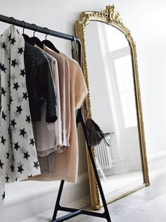 I like the idea of a floor-length mirror next to an open clothing rack. It gives the room a gallery/dressing room feel.