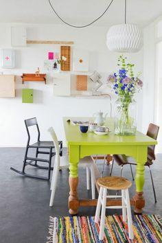 table en bois peint en vert, chaise bercante, fleurs sur la table, sol en beton ciré
