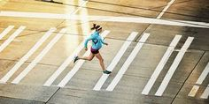 Pregnant woman running across sidewalk during early morning run on empty city street