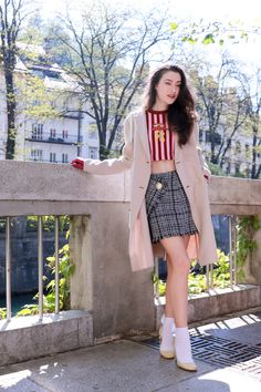 Fashion blogger Veronika Lipar of Brunette From Wall Street sharing how to style short white bow socks, mini skirt and striped crop top on a cold spring day