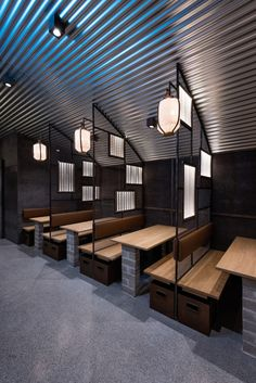 Industrial Interior Design - This Restaurant and bar goes for a warehouse chic style with metal, concrete, and wood. In this modern restaurant, a neutral palette was created through the use of rusty looking steel, concrete bricks, and the galvanized steel roof. Metal dividers with lighted boards in them separate the tables at the front of the restaurant and feature hanging lanterns to help set the mood.