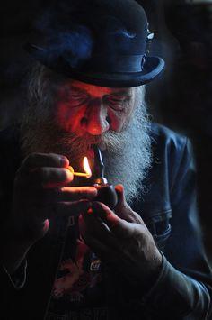 old man lighting pipe