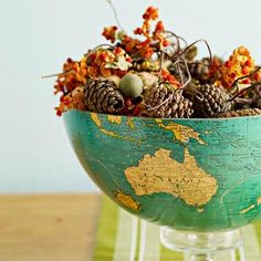 Reimagine an old globe as a new centerpiece. Split a globe in half and fill it with flowers or other collections—we used pinecones, acorns, seedpods, small pumpkins and bittersweet. Elevate on a short candlestick or small serving dish as a centerpiece.