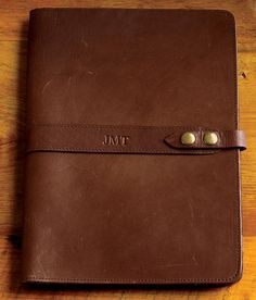 """Get organized and look good doing it with this leather executive portfolio. Made from genuine native American steer hide, this portfolio features a two-position solid brass snap closure that allows room for extra documents. Edge stitched with an inside front diagonal pocket and center pencil slot. Pencil and memo pad included. Accommodates standard 8½"""" x 11"""" ruled pad. Leather executive portfolio in brown. 9½""""L x 12""""W. USA."""