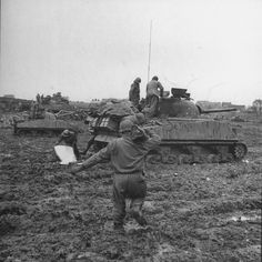 American soldier carrying ammunition to a Sherman tank, 3rd Armored Division, during the battle for the Strolberg area of Germany, 1944