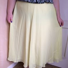 Yellow skirt Bright and pretty! It's a lemon yellow color. The second picture shows the correct color. Flowy chiffon material. The waistband is stretchy. It's marked as 24 but fits 2x better. New with tags. It goes about to my ankles. I'm modeling as 18/20, 40 f/g, 5'7. Roaman's Skirts