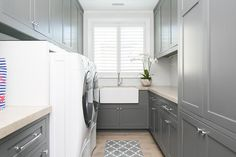 Gray laundry room features gray shaker cabinets paired with light gray countertops and a white linear tiled backsplash.