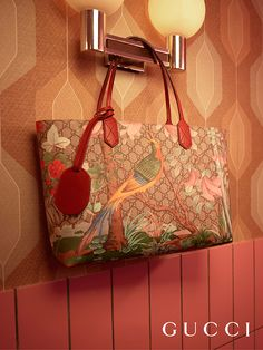 The bird and plants on this Gucci Tian tote color the House's GG motif in brushstroke style graphics, creating a three-dimensional effect. Designed by Alessandro Michele, the bag features red leather trim.