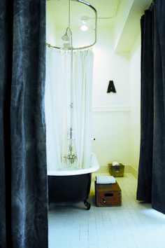 """Claw foot tub painted in high-gloss black, black canvas curtains in    Ace Hotel, Portland.  """"For something similar, consider sourcing a Black Canvas Drop Cloth for $24 from Homestead.."""""""