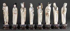 Another set of Eight Chinese Stained Ivory figures of the Eight Daoist Immortals, each standing figure carved with its attribute: He Xiangu with a lotus flower, Cao Guojiu with castanets, Tieguai Li with an old crutch, Lan Caihe with a flower basket, Lu Dongbin with a sword, Han Xiang with a flute, Zhang Guo with a fish drum, and Zhongli Wuan with a fan.