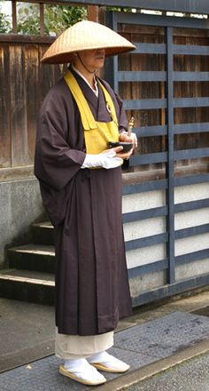 """The """"bib"""" worn by the Japanese monk is a rakusu, a garment unique to the Zen school that may have originated among Ch'an monks in China sometime after the T'ang Dynasty. Generally in Zen, the rakusu may be worn by all monks and priests, as well as laypeople who have received jukai ordination. The monks' straw hat is worn to partly cover his face during the alms ritual, or takahatsu, so that he and those who give him alms do not see each others' faces. This represents the perfection of giving…"""