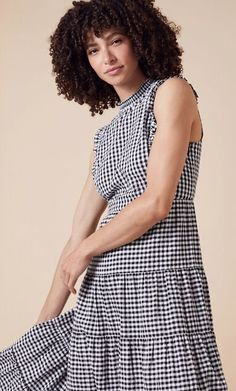 Gingham is so easy to wear, and the perfect print for summer. This midi-length dress is designed in light, organic cotton with a high neckline, tiered skirt and a slim frill along the armholes.   Breathable, light and soft to the touch, our organic cotton is grown using methods and materials that are kinder to the environment. It avoids toxic pesticides and synthetic fertilisers which makes production safer for people and wildlife.