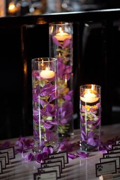 ALTERNATE CENTERPIECE IDEA: 3 cylindrical vases in varying heights. Tall and short vases contain marbles and candles. Medium vase contains flowers, marbles and submersible lights.