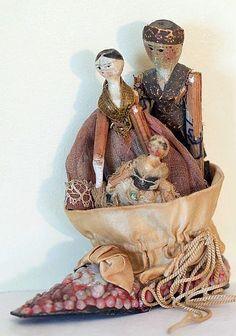 Three primitive Grodnertal dolls in a shell shoe