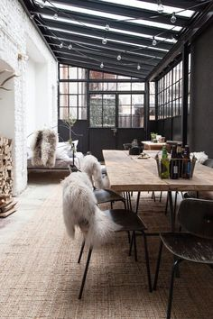 To create a very contemporary take on the conservatory, choose rustic modern pieces, sisal flooring and exposed brick walls. Industrial steel windows are softened with sheepskin and other natural textures.