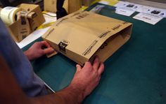 An employee seals a packaged customer order into an Amazon branded cardboard delivery box ahead of shipping at one of Amazon.com Inc.'s fulfillment centers.
