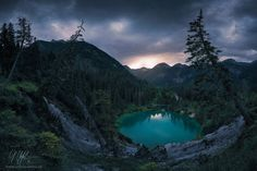 """Hidden Crater Lake - """"Hidden Crater Lake"""" - Tyrol - Austria  Deep in the wooded valleys of Tyrol lies this round and crazy-colorful crater-lake. No track leads to the edge of this little pearl. While dark clouds moved across the sky that evening, the last light of the sun could dip the horizon in a bit of color for a moment. What a valuable discovery for me.  <a href=""""www.rheinwerk-verlag.de/3728"""">CHECK OUT MY NEW BOOK</a>  Prints and licensing available.  <a…"""