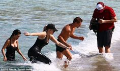 Hard at work: Kim's sisters Kourtney and Khloe took a fully clothed dip as they got in som...