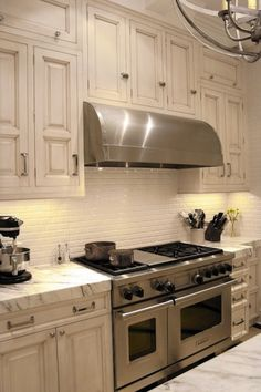 Calacatta marble countertops, limestone floors with wood pickets, ivory subway tile from Urban Archeology and custom antique white burnished / glazed cabinetry #Kitchen Lab