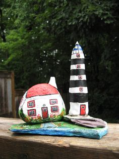 A lighthouse made of modelling clay and a stone house are painted with acrylic paint and mounted