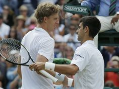 Novak Djokovic, right, shakes hands at the net with Kevin Anderson after their match.  Alastair Grant, AP