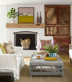 The owner of this California ranch accented her white fireplace with a wood mantel, a warm-colored painting, and vases.    - CountryLiving.com