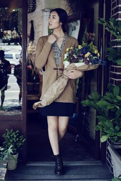 Liu Wen wearing a luxurious cashmere cardigan in camel over a stretchy black mini skirt