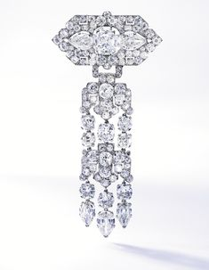 AN ELEGANT PLATINUM AND DIAMOND BROOCH, CARTIER, FRANCE Suspending an articulated pendant of geometric design, the top centered by an antique cushion-cut diamond weighing approximately 5.30 carats, the top and fringes accented by five pear-shaped diamonds weighing approximately 6.50 carats, further set with numerous old mine and single-cut diamonds weighing approximately 22.00 carats, signed Cartier, Made in France, numbered 5904C; circa 1925.