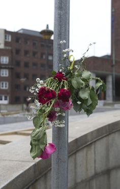 """""""Grief in the public domain"""". Flowers tied to a post outside Oslo City Hall. Datering 2011"""