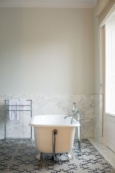 Bathroom Photo - A clawfoot tub in a marble bathroom with a tiled floor