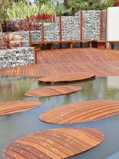 This unique design incorporates unusual media and materials to provide a backyard that will leave your guests talking. Stained and shaped wooden islands provide a pathway over a shallow pond, and incorporate well into the unique decking and stone garden bed borders.
