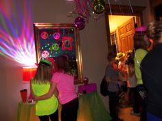 This was one of my favorites.  I decorated the entry table with a cute lamp that had a disco light bulb in it.  I painted the mirror with neon window paint and taped pictures of the b-day girl on it for people to look at.  I placed a box on the table for all of the b-day cards to go into when the guests arrived.  I also underlit the table so that it glowed green.
