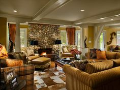 This lodge-style living room features a custom stone fireplace complete with a skeleton stone pattern and an extended candle ledge above it. The classic mix of comfortable seating showcases a pair of custom-designed wingback chairs and sofa pillows that are trimmed with real feathers to add to the lodge-style look.