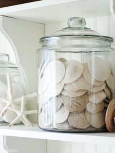 DIY Bathroom Linen Shelves - Ella Claire - use an oversized glass canister to display sand dollars. Informations About DIY Bathroom Li - Beach Cottage Style, Coastal Cottage, Coastal Homes, Beach House Decor, Coastal Style, Coastal Decor, Home Decor, Coastal Bathroom Decor, Coastal Entryway