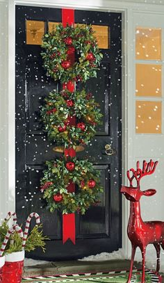 Make your first impression extra jolly with the professionally decorated look of three wreaths on a red velveteen ribbon.
